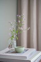 Asters in a glass vase and an earthenware bowl on a stack of coffee-table books