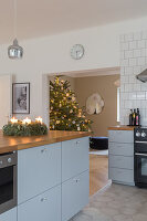 An Advent wreath on grey-blue kitchen island with a wooden worktop with a Christmas tree in the background