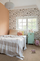A bed and a mint green bedside table in a child's room with wallpaper and an apricot-coloured wall
