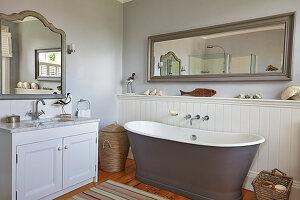 Frei stehende Badewanne, Waschtisch und Wandspiegel im Badezimmer