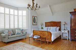 Spacious bedroom with wooden bed and sofa