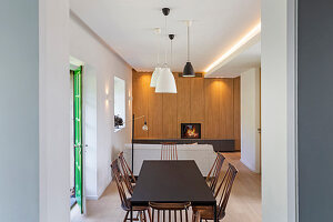Dining area in open-plan interior with fitted cupboards in the background