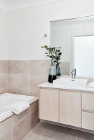 Washstand with countertop sink next to bathtub in bright bathroom