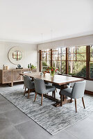 Wooden dining table and grey upholstered chairs next to window