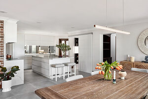 View across dining table into open-plan kitchen with island counter