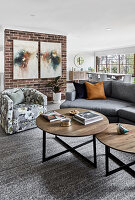 Coffee table, sofa and armchair in front of brick wall in living room