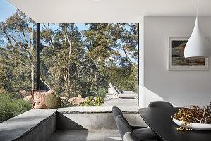Elegant dining area with masonry window seat running along panoramic glass walls