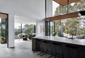 Long kitchen island with bar stools in high-ceilinged interior with glass walls