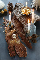 DIY Advent arrangement on tree bark decorated with burning candles on grey wood and gold Christmas tree decorations