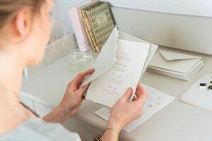 Blonde Frau liest Brief am Schreibtisch
