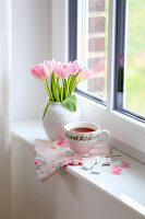 Vase mit Tulpenstrauß und Teetasse auf Fensterbank