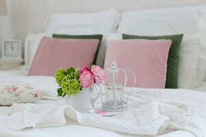 Tablett mit Blumen auf Doppelbett mit weißer Decke