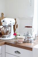Teekessel, Teetassse und kleiner Blumenstrauß neben Küchenmaschine