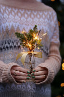 Woman holds posy of spruce branches and sparklers