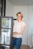 Blonde woman holding book stood next to open cupboard