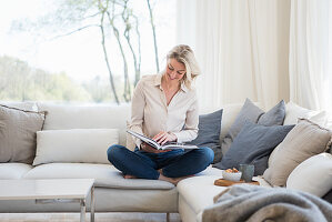 Blonde woman reading a book while sitting on comfortable sofa