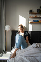 Blonde woman sitting with book on the bed
