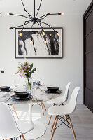 Round dining table and white classic chairs below pendant lamp