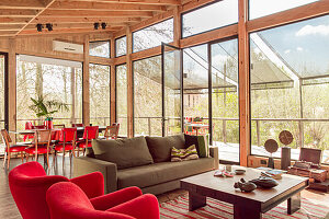 Upholstered furniture in red and taupe and a coffee table in weekend house with glass walls