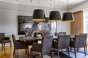 Dining table and grey upholstered chairs below large lampshades