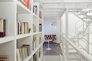 Bookcase, side table and easy chair on mezzanine with white iron structure