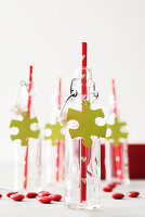 Swing-top bottles with red straws and jigsaw-piece pendants