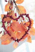 Rose hip heart on artificial branch with autumn leaves