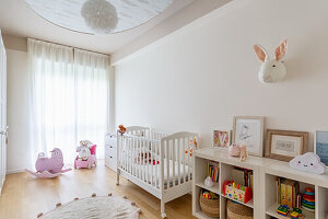 Bright nursery with cot and pink rocking animal
