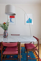 Arc lamp over dining table with marble top and upholstered chairs