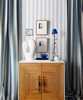 Cabinet with blue and white decorative objects flanked by blue and white striped curtains