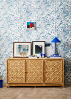 Small cabinet in front of wall with blue and white wallpaper