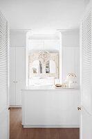 Blick in weißes Umkleidezimmer und Badezimmer