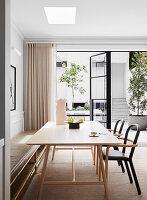 Esstisch mit Stühlen und Sitzbank vor Terrassentür