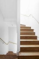 Holztreppe in weißem Treppenhaus