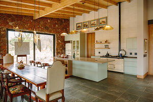 Open kitchen with kitchen island and dining area with long wooden table