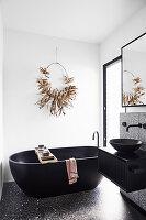 Schwarze, freistehende Badewanne vor weißer Wand