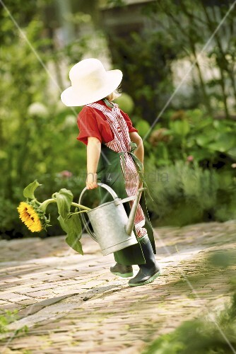 A little girl dressed as a gardner holding a watering can and a sunflower