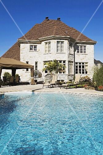 imposanter pool vor stattlichem haus mit gro er steinterrasse bild kaufen living4media. Black Bedroom Furniture Sets. Home Design Ideas