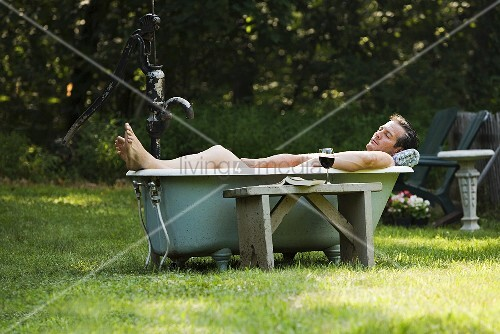 Man in outdoor bathtub