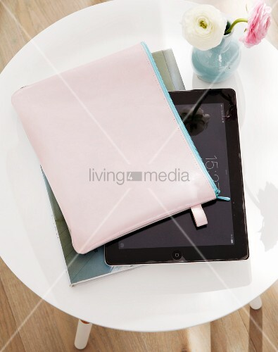 A tablet PC with a homemade, goat's leather case and daisies on a side table