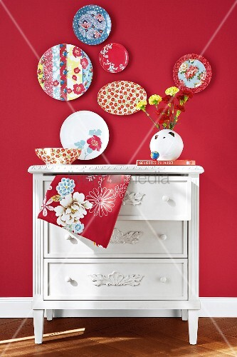 Decorative plates on red wall above white chest of drawers