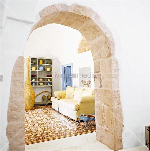 Blick durch Rundbogen aus Kalksteinquadern in ein Wohnzimmer mit Fliesenboden – Bild kaufen ...