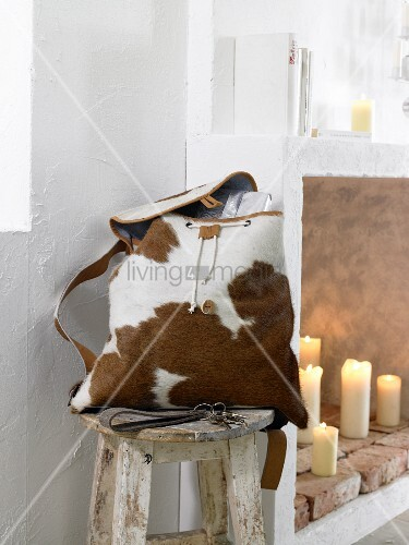A cowhide backpack on a rustic wooden stool next to a wall niche with candles