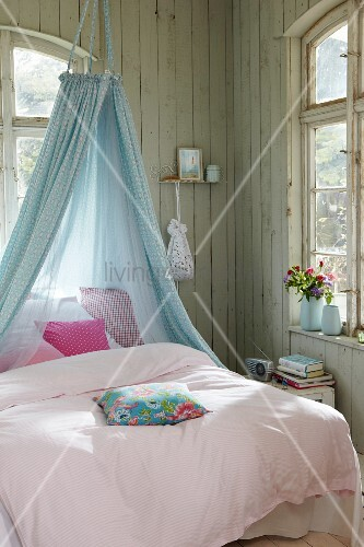 Fabric canopy above bed in wooden cabin