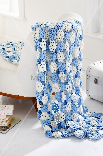 Blue and white blanket of crocheted flowers