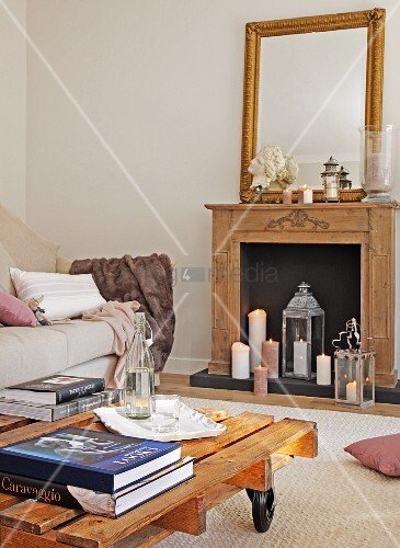 Table made of pallet on castors and pale sofa in front of lit candles in fireplace below wall mirror on mantelpiece