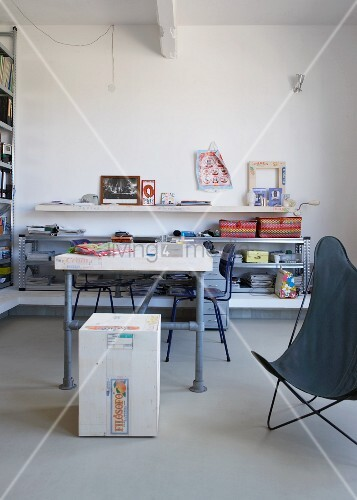 DIY table made of scaffolding poles in front of half-height shelving in minimalist interior