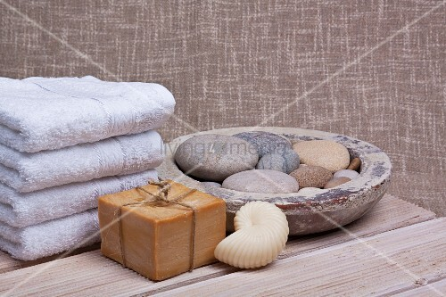 Spa - soaps and towels next to bowl of pebbles