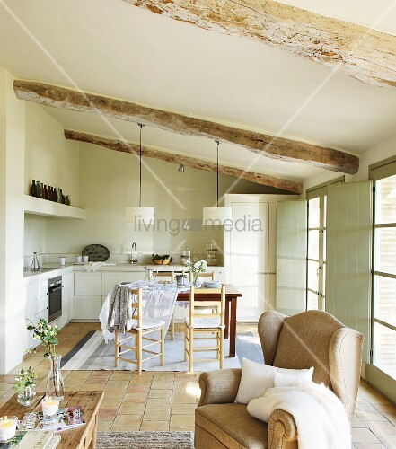 View past wingback armchair to dining table in open-plan kitchen of simple country house