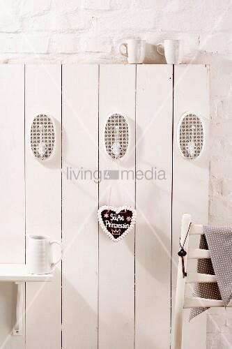 weisse holzwand mit haken und lebkuchenherz bild kaufen living4media. Black Bedroom Furniture Sets. Home Design Ideas